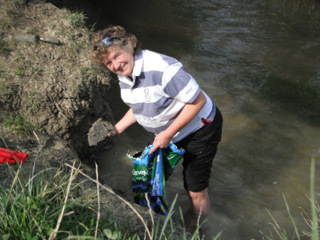 Bridget Macklin collecting clay from the bank of a river